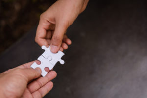 Hands with puzzle pieces to build trust in relationships